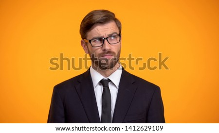 Pensive male thinking about business ideas for start up, orange background