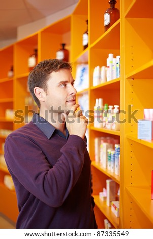 Pensive man buying some medicine in a pharmacy