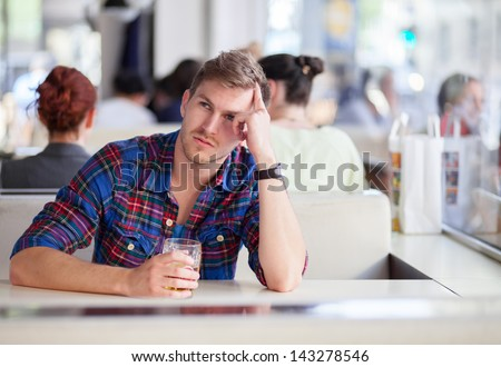 Pensive man drinking beer in a bar