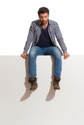 Pensive man in boots, jeans and lumberjack shirt is sitting on a top and looking down. Full length studio shot isolated on white.