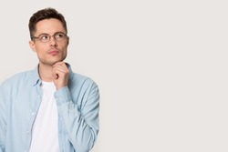 Pensive man in glasses isolated on grey white blank pose look aside at empty copy space touch chin lost on thoughts thinking planning future, makes important decision feels doubtful and unsure concept