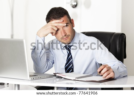 pensive man in office with computer and pen