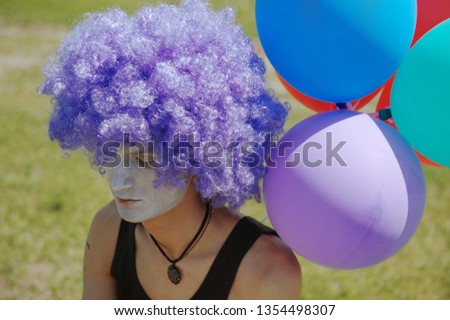 Pensive man in the clown costume next to the colorful balloons