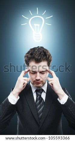 pensive man with a drawing lamps over his head - stock photo