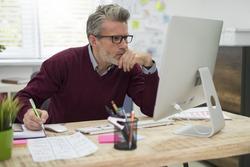 Pensive man working hard on computer