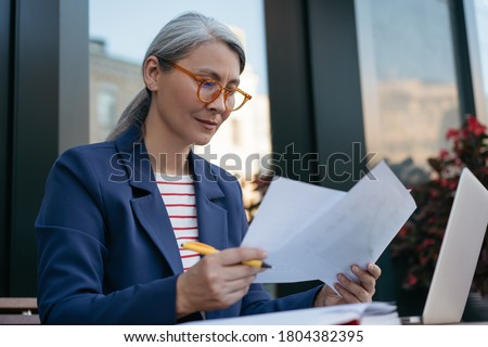 Pensive mature businesswoman reading contract, planning project, brainstorming. Portrait of middle aged asian secretary reading, working with documents, sitting at workplace