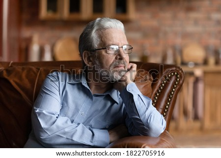 Pensive mature Caucasian grey-haired man relax on sofa in living room look in distance thinking dreaming. Thoughtful senior 70s grandfather rest on couch at home, lost in thoughts remembering missing.