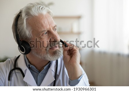 Pensive mature male doctor in earphones consult patient online look in distance thinking pondering. Thoughtful senior man GP in headphones talk on video call make decision. Virtual event concept.