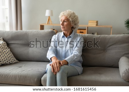 Pensive mature woman sit on sofa in living room look in distance window thinking of lonely life, thoughtful elderly female rest on couch at home feel melancholic, miss old days, solitude concept