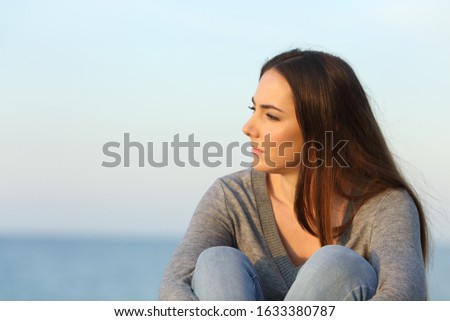 Pensive melancholic woman looking away sitting on the beach at sunset