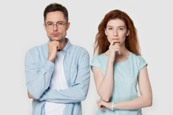 Pensive millennial couple stand isolated on grey studio background touch chin with finger thinking of something, thoughtful man and woman consider or plan idea, look at camera lost in thoughts