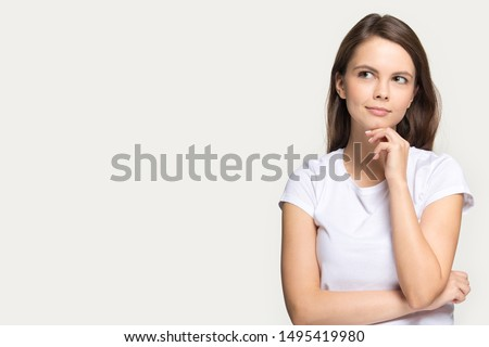 Photo of Pensive millennial girl isolated on grey studio background thinking looking at blank copy space aside, thoughtful young woman touch chin pondering over sale offer, consider promotion or deal