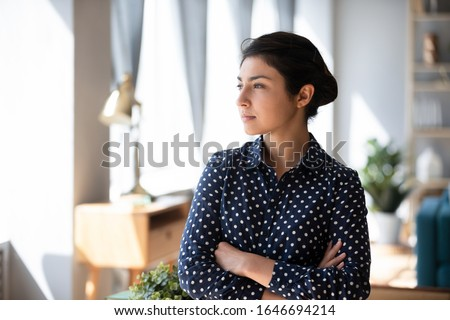 Pensive millennial Indian girl stand in living room look in window distance thinking or making decision, thoughtful young ethnic woman lost in thoughts pondering planning, remembering or recollecting