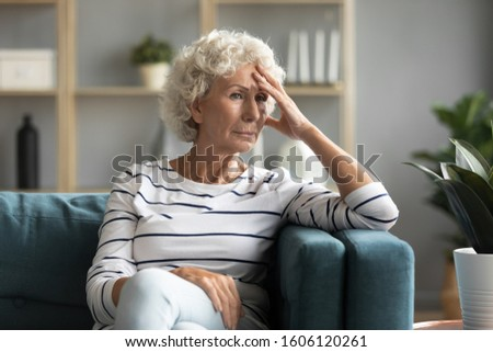 Pensive 70s woman sitting on couch thinking about difficulties of life personal failure bad period, health problems feeling fatigue and tiredness resting at home, in sad thoughts and troubles concept