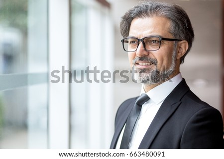 Pensive senior man in glasses looking out window - Shutterstock ID 663480091
