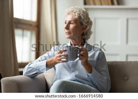 Pensive senior 60s woman sit rest on couch in living room drink tea or coffee look in distance thinking, thoughtful dreamy mature grandmother lost in thoughts, pondering dreaming at home