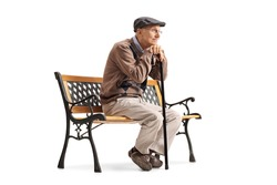 Pensive senior with a walking cane sitting on a bench isolated on white background