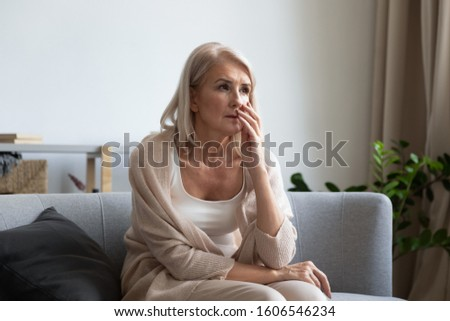 Pensive senior woman grandmother sit on couch look in distance thinking or remembering, thoughtful mature female pensioner or retiree feel sad lonely mourning yearning at home, solitude concept