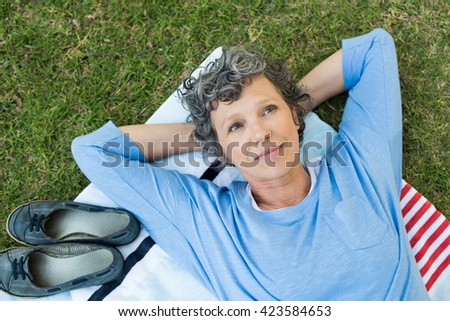 Pensive senior woman lying on towel on grass. High angle view of thoughtful mature woman thinking. Retired woman contemplating her life after retirement.