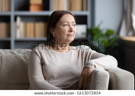 Pensive senior woman sit on sofa in living room look in window distance thinking pondering, thoughtful middle-aged female rest on couch at home lost in thoughts dreaming or remembering