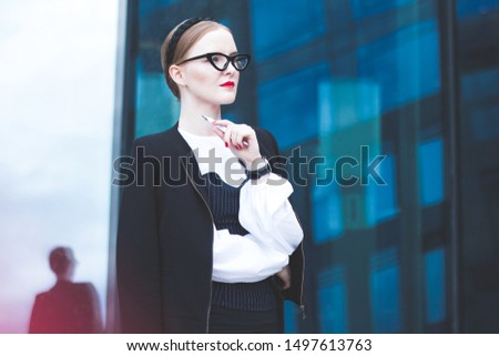Pensive, Serious businesswoman with a pensive look standing outdoors, looking into the distance with glasses, a formally dressed woman outside the office building holds a pen in her hands.