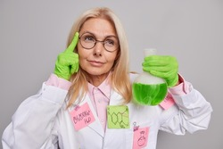 Pensive skilled female chemist researches chemical substance keeps finger on temple has clever look performs experiment in laboratory wears round spectacles white medical coat studies biochemistry