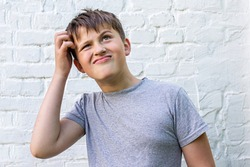 Pensive smiling boy is wistfully scratching his head. schoolboy remember something, having thoughts. Thinking concept