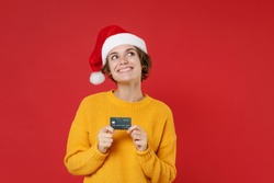 Pensive smiling young Santa woman in casual yellow sweater Christmas hat hold credit bank card looking up isolated on red background studio portrait. Happy New Year celebration merry holiday concept