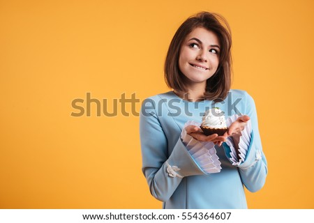 Pensive smiling young woman holding cupcake and thinnking