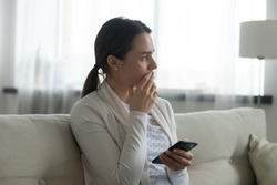 Pensive stressed young Caucasian woman sit on sofa at home using cellphone look in distance pondering of problem. Anxious millennial female feel distressed frustrated with message or text