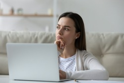 Pensive student girl sit in front of laptop thinking over task do assignment distracted form study. Young concerned woman deep in their thoughts frown searching issue problem decision look in distance