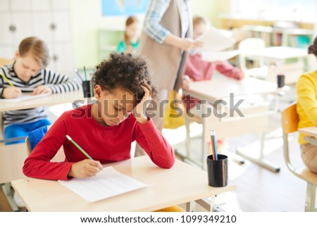 Pensive student of elementary school leaning over his copybook while ticking right answers in test #1099349210