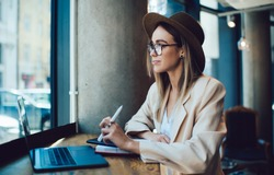 Pensive stylish lady in hat and glasses holding pen and looking away while sitting at restaurant table with laptop while sitting near window