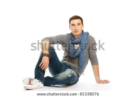 Pensive stylish young man sitting on floor and looking at copyspace