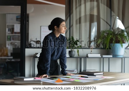 Pensive successful young indian businesswoman stand at workplace look in distance planning or thinking of career success. Thoughtful ethnic woman dream visualize in office. Business vision concept.