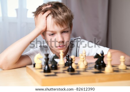 Pensive teenager playing chess in room