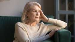 Pensive thoughtful middle aged lady looking away sit alone at home feel anxious lonely, sad depressed melancholic old mature woman suffer from sorrow grief thinking of problem suffer from solitude