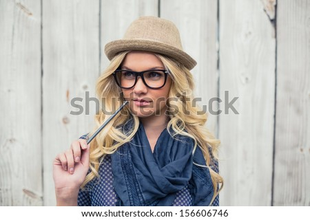 Pensive trendy blonde holding pencil on wooden background
