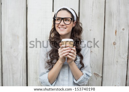 Pensive trendy woman with stylish glasses holding coffee posing on wooden background