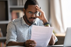 Pensive unhappy biracial man in glasses feel distressed reading bad news in paperwork letter, disappointed frustrated African American male confused by unpleasant postal correspondence or notice