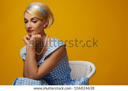 Pensive woman in a blue dress sitting