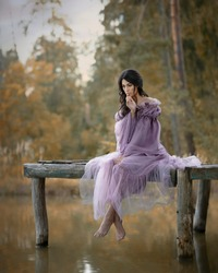Pensive woman in a pink dress on the bridge in the autumn forest