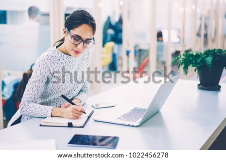 Pensive woman in eyewear planning working schedule writing in notebook while sitting at working place with laptop computer,female administrative manager making notes of information browsed on netbook