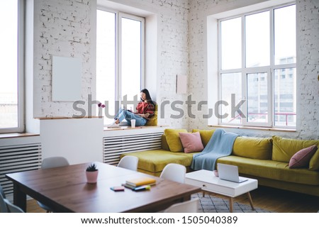 Pensive woman in glasses wearing casual clothes writing notes in textbook while sitting on windowsill next to flowers in modern apartment