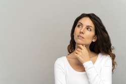 Pensive woman keeps finger on chin, concentrated and ponders, wears white T-shirt with long sleeves, look up at blank copy space. Girl thinking over sale offer making choice, looking aside. Mock up.