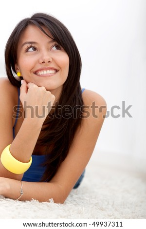 Pensive woman lying on the floor and smiling