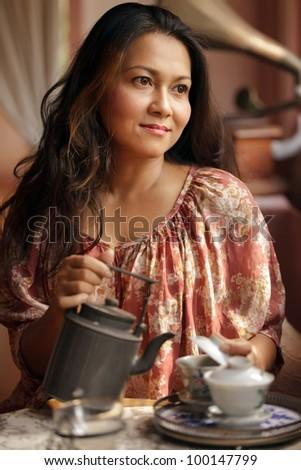pensive woman  pouring tea in cup in retro interior