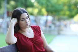 Pensive woman sitting on a bench in a park looking away