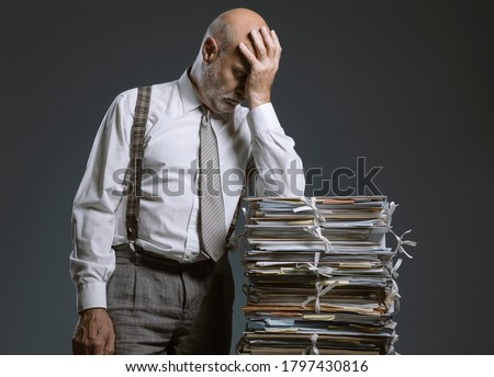 Pensive worried businessman leaning on a pile of paperwork, bureaucracy and administration concept Stock photo ©