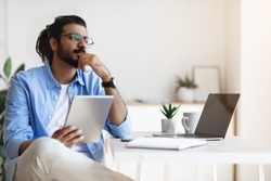 Pensive Young Arab Male Freelancer Using Gigital Tablet And Daydreaming At Home, Handsome Eastern Man Thinking About New Business Ideas, Sitting At Desk Touching Chin And Looking Aside, Free Space